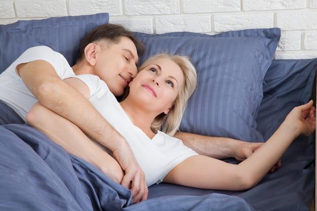 Starsza para w łóżku w domu.