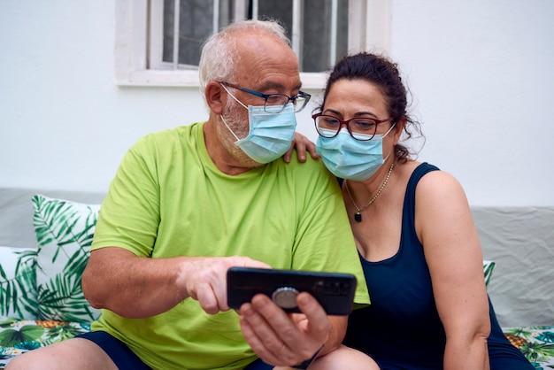 Starsza para w maskach na twarz i rozmowa wideo za pomocą tabletu