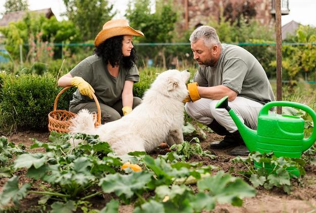 Starsza para w ogródzie z psem