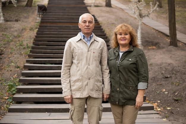 Starsza para w parku jesienią, para starszych relaks w okresie wiosenno-jesiennym. styl życia w opiece zdrowotnej