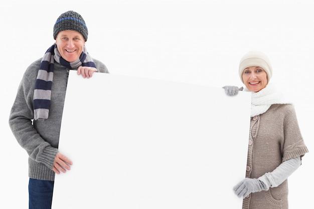 Starsza para w zimowe ubrania gospodarstwa karty