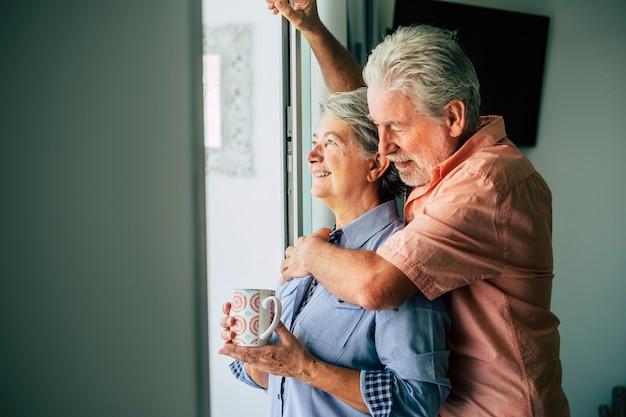 Starsza para wygląda przez okno