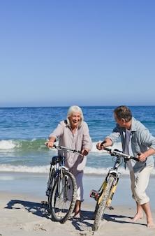 Starsza para z ich rowerami na plaży