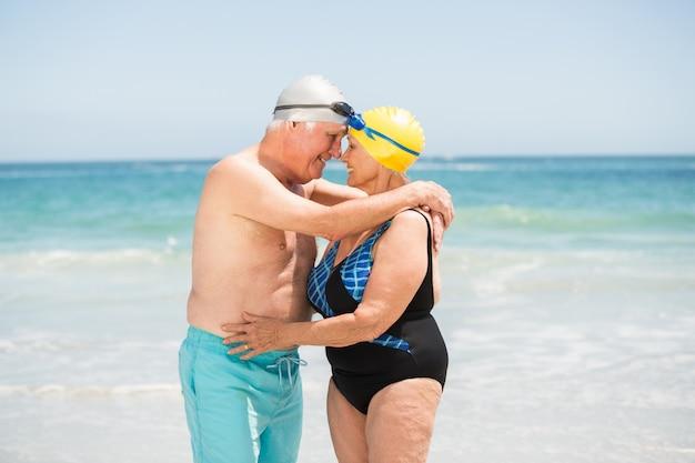 Starsza para z kąpanie nakrętką przy plażą
