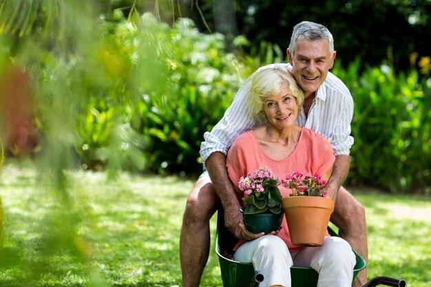 Starsza para z kwiat garnkami w jardzie