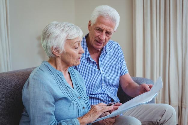 Starsza para z rachunkami podczas gdy siedzący na kanapie