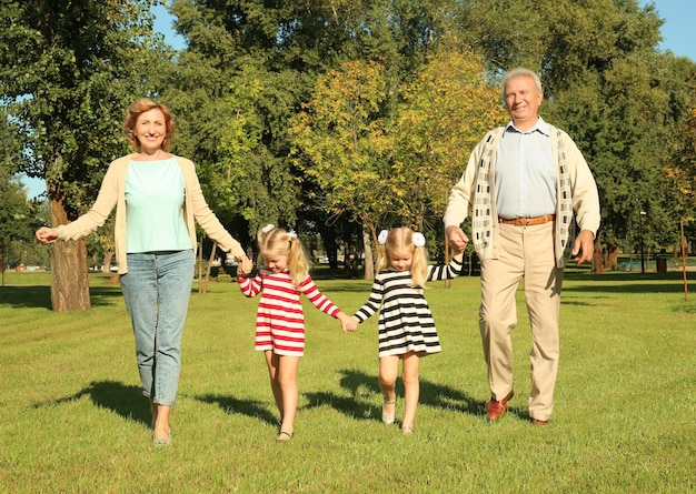 Starsza para z wnuczkami w parku