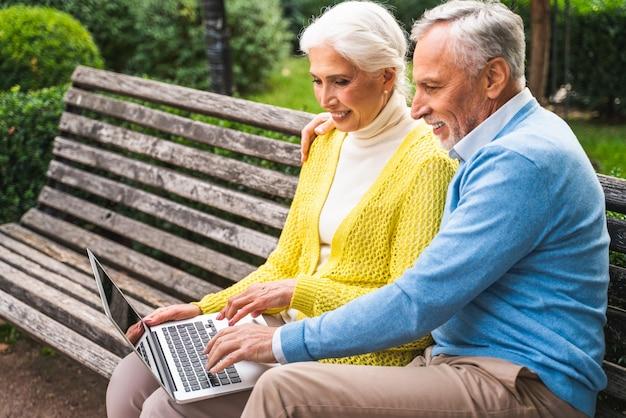 Starsza para za pomocą komputera przenośnego na ławce