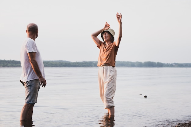 Starsza para zakochana, tańcząca i chodząca po nabrzeżu morza lub rzeki w letnim zachodzie słońca tim