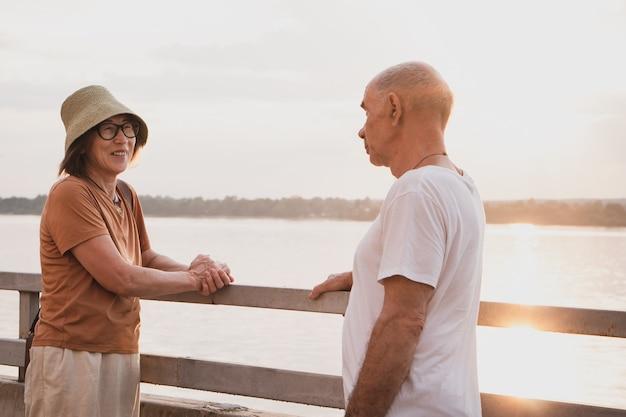Starsza para zakochanych, patrzących na siebie, stoi blisko brzegu rzeki