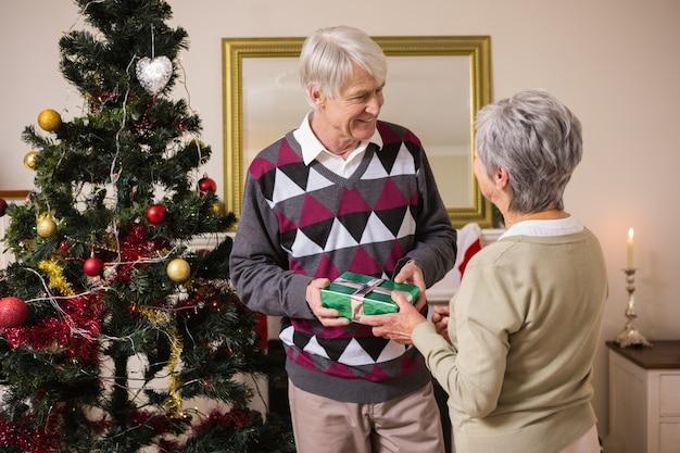 Starsza para zamiata prezenty ich choinką