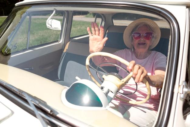 Starsza podróżniczka w czerwonych okularach przeciwsłonecznych obok samochodu
