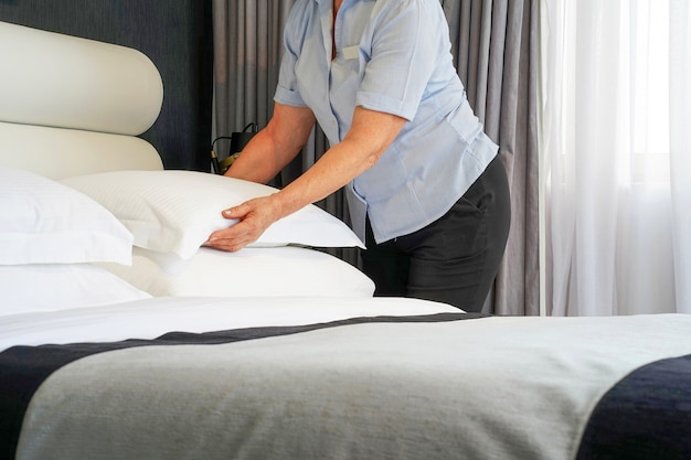 Starsza pokojówka robi łóżko w pokoju hotelowym. housekeeper making bed