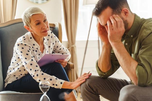 Starsza psychoterapeutka pociesza sfrustrowanego, ciemnowłosego, młodego pacjenta płci męskiej rasy kaukaskiej podczas sesji terapeutycznej