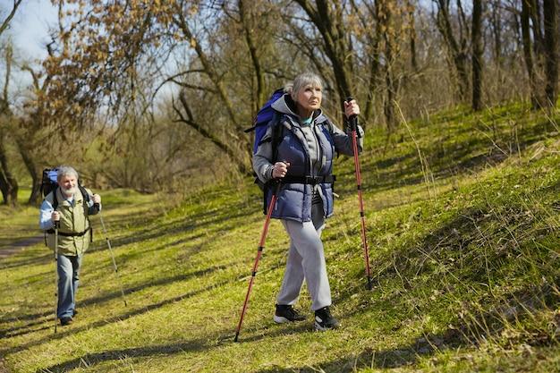 Starsza rodzina para mężczyzny i kobiety w strój turystyczny spaceru na zielonym trawniku w słoneczny dzień