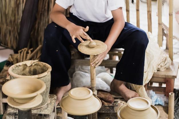 Starsza rzemieślnicza azjatykcia garncarka robi glinianemu garnka ziemnemu garncowi ręcznie.