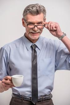 Starsza samiec w szkłach z filiżanką kawy.