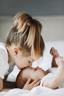 Starsza siostra całuje małą córeczkę w czoło z zamkniętymi oczami