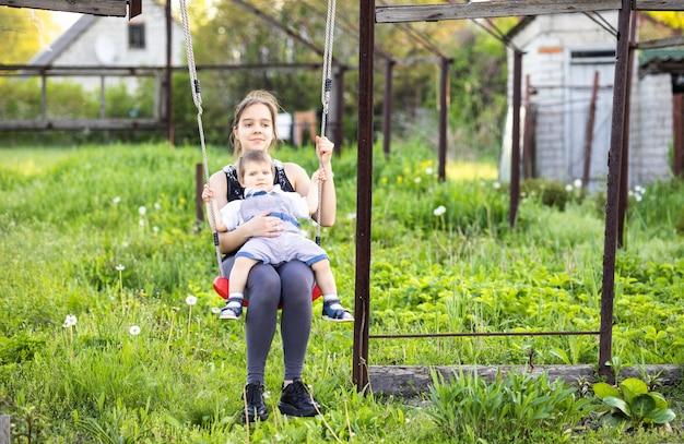 Starsza siostra jest w ciemnych wiosennych ubraniach, a jej młodszy brat to maluch w jasnym kombinezonie. jeździ na nim na czerwonej huśtawce i cieszą się wiosną w kwitnącym ogrodzie w ciepłą wiosenną pogodę.