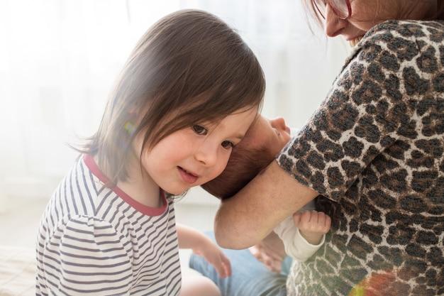 Starsza siostra przytula nowonarodzoną siostrę. babcia trzyma w ramionach nowonarodzoną wnuczkę