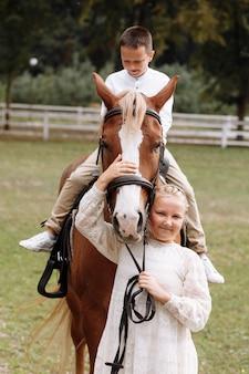Starsza siostra spaceruje z młodszym bratem na koniu na farmie w letni dzień. rodzeństwo spędzające czas na wakacjach. szczęśliwa rodzina koncepcja.