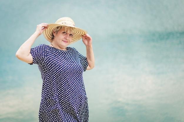 Starsza siwowłosa kobieta w słomkowym kapeluszu, stojąca nad wodą i wyglądająca na szczęśliwą i pozytywną.