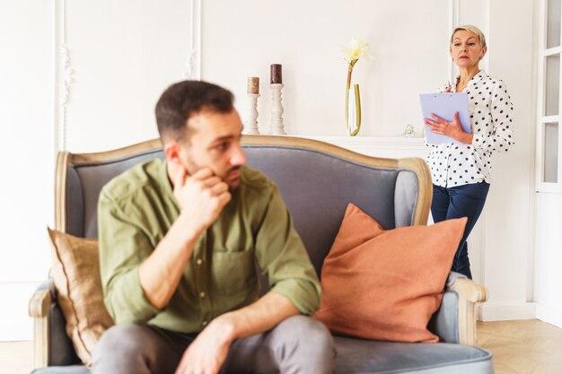 Starsza skoncentrowana psychoanalityczka ze schowkiem w dłoni, stojąca za pacjentem
