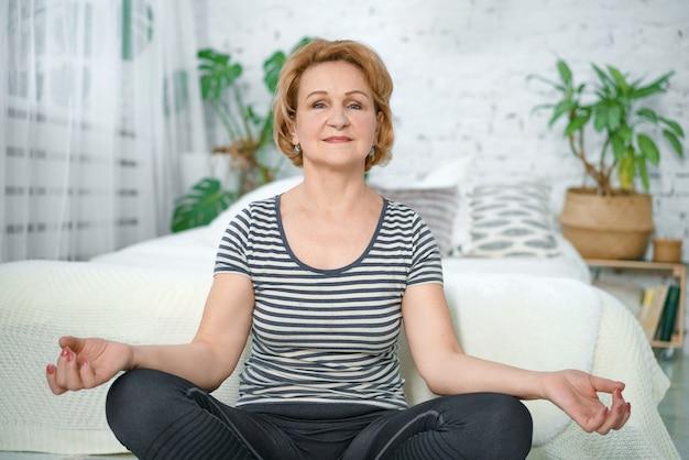 Starsza spokojna kobieta medytuje w domu w pozycji lotosu.