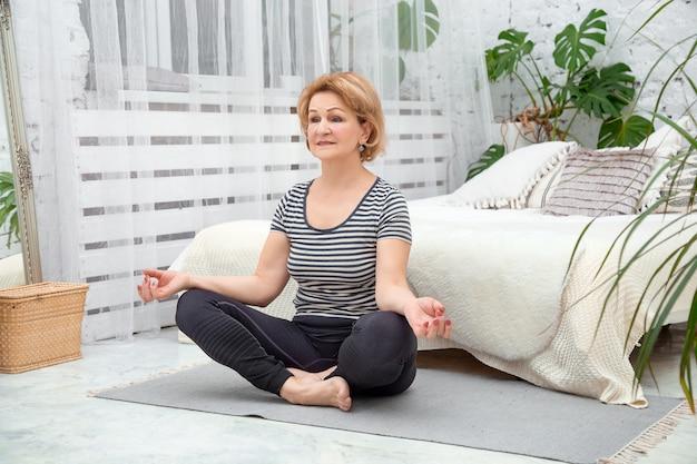 Starsza spokojna kobieta medytuje w domu w pozycji lotosu