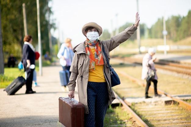 Starsza starsza kobieta w kapeluszu i masce medycznej czeka na pociąg, zapobieganie wirusom i infekcjom