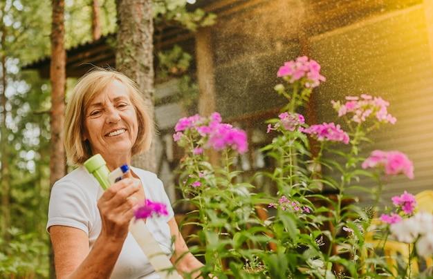 Starsza starsza ogrodniczka rolnik kobieta dbająca o kwiaty w letnim ogrodzie na wsi na zewnątrz spraye