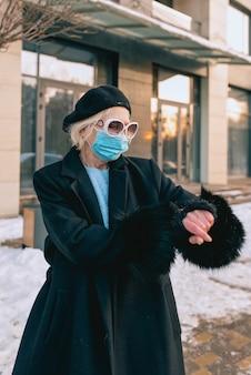 Starsza stylowa kobieta w masce medycznej spacerująca na świeżym powietrzu i odliczająca czas do końca pandemii