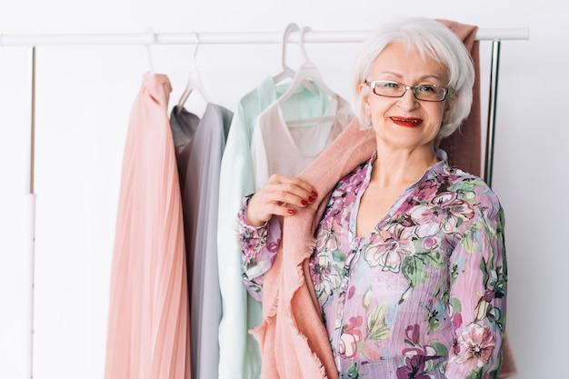 Starsza szafa pani. opcje zakupów i odzieży. uśmiechnięta starsza kobieta wybierając modny strój.