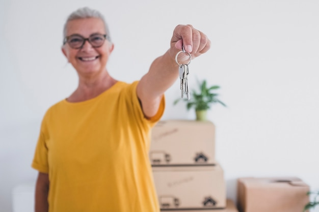 Starsza szczęśliwa kobieta trzymająca klucze nowego mieszkania stojącego w pustym domu z ruchomymi pudłami na podłodze - koncepcja aktywnych starszych emerytów cieszących się nowym życiem