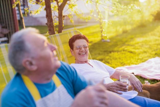Starsza szczęśliwa para odpoczywa w krześle na ich podwórku