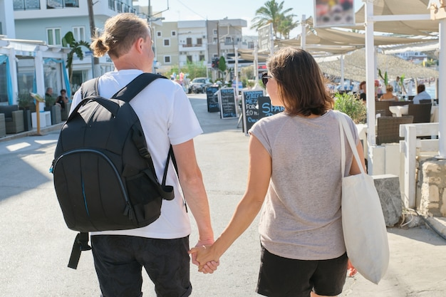 Starsza szczęśliwa para spaceru po kurorcie, trzymając się za ręce