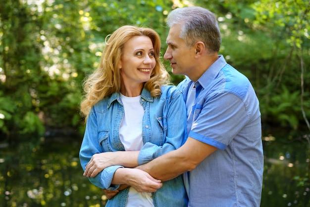 Starsza szczęśliwa para stoi w lesie w słoneczny dzień i przytulić. pojęcie szczęśliwych relacji rodzinnych. romans w dobie