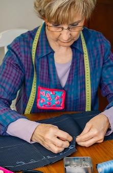 Starsza szwaczka szyjąca materiał, aby uszyć ubranie w swoim warsztacie