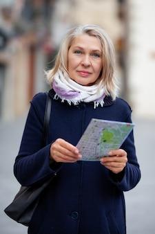 Starsza turystka spaceruje ulicami miasteczka z mapą w ręku.