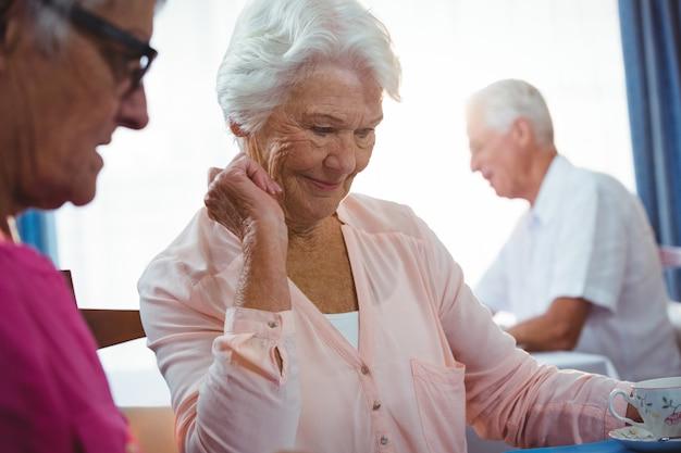 Starsza uśmiechnięta kobieta z filiżanką kawy