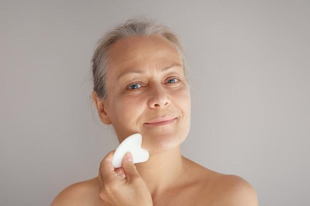 Starsza uśmiechnięta siwowłosa kobieta masuje twarz jadeitową deską odizolowaną na szarym tle