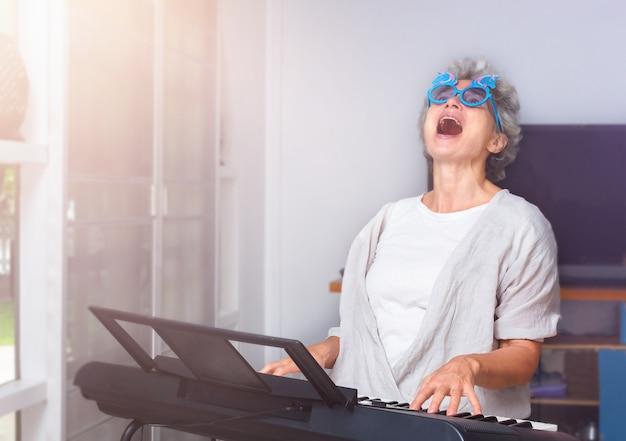 Starsza wesoła kobieta grająca na pianinie, tańcząca i śpiewająca