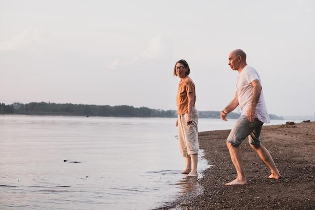 Starsza wielorasowa para zakochana spędzająca czas w rzece lub brzegu morza w lecie