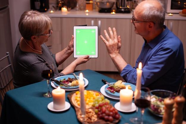 Starsza żona i mąż macha na komputerze typu tablet z zielonym ekranem. ludzie w podeszłym wieku patrzący na zielony ekran szablonu chroma key, siedzący przy stole w kuchni podczas kolacji.