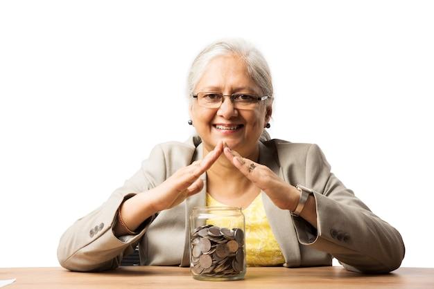 Starsze indyjskie lub azjatyckie kobiety biznesu oszczędzające lub trzymające lub obliczające monety walutowe. koncepcja biznesowa, finansowa i inwestycyjna