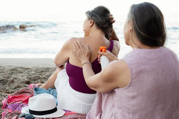 Starsze kobiety nakładają krem przeciwsłoneczny na plecy na plaży