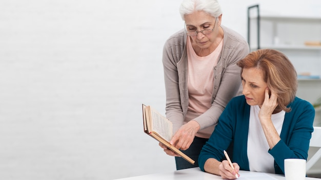 Starsze kobiety patrzeje w książkę