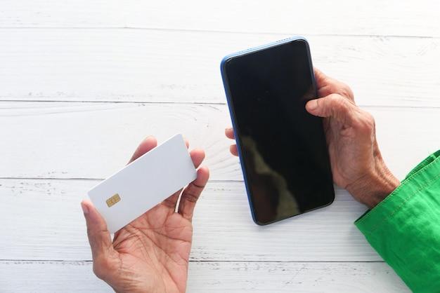 Starsze kobiety ręka trzyma kartę kredytową i za pomocą inteligentnego telefonu zakupy online.