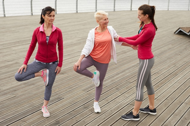 Starsze kobiety robi joga na molo