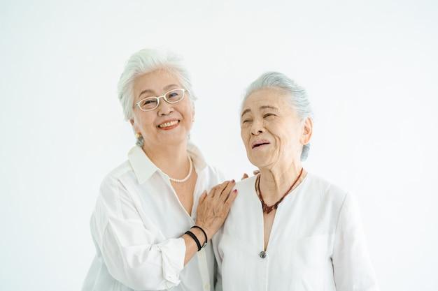 Starsze kobiety rozmawiają z uśmiechem w jasnym pokoju